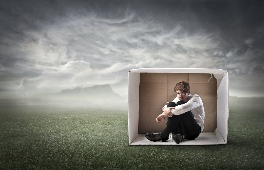 Sad young businessman sitting in a carton on a green meadow under stormy sky